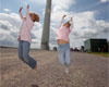 Two children jump for joy in front of one of our turbines