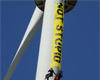Climbers hang a 'Not Stupid' banner from our Ecotech turbine.