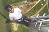 Shows Dale Vince abseiling down a wind turbine.