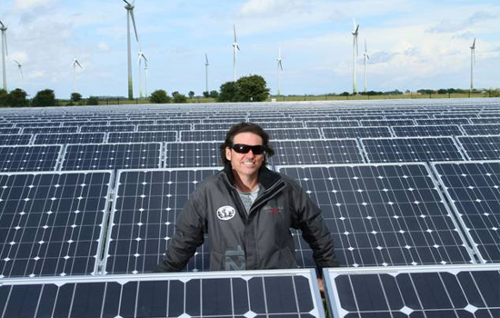 Dale Vince in the middle of a field of solar panels, with wind turbines in the distance