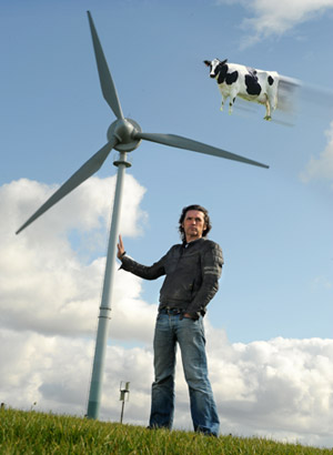 Dale Vince in front of one of our turbines... with a flying cow?
